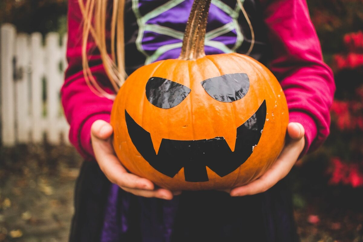 girl holding painted pumpkin