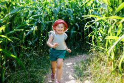 girl running through corn maze smiling